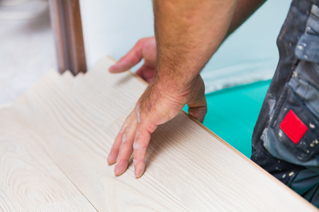 wood flooring: Handyman renovating house, installing laminate wood flooring with care. Stock Photo