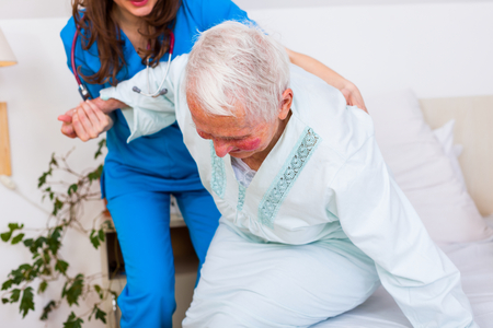 Elderly patient starting to wal, a beautiful brunette geriatric doctor helping her first steps.