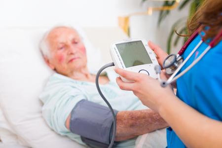 Geriartric doctor measuring senior womans blood pressure - blank LCD display.