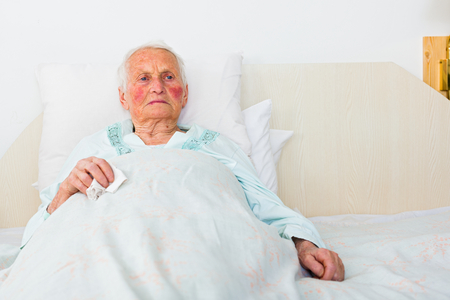 elderly woman laying sad in bed waiting for doctor.