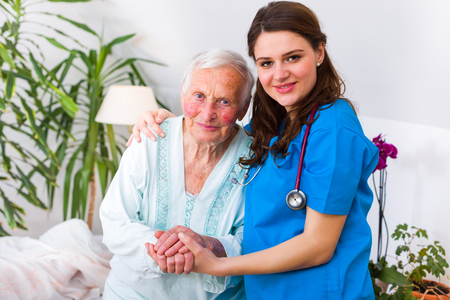 Caring nurse supporting her patient when she is getting up from bed after long time of illness. Archivio Fotografico