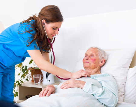 Young nurse examining an elderly woman with stethoscope, lustening to the lung and heart sounds. Stock Photo