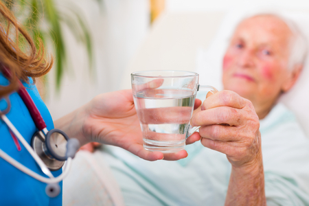 Doctor giving sick senior woman a glass of water to help her get better. Stock Photo