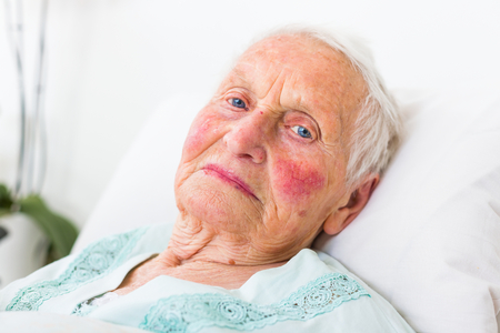 pacientes: Un retrato de una anciana de ojos azules sentar en la cama. Foto de archivo