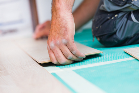Handymans dusty hands laying down laminate wood flooring boards, mounting them together with great care.