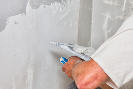 Construction worker holding plastering trowel, smoothing wall defects. Archivio Fotografico