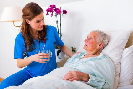 Kind geriatrische arts brengt water naar de senior vrouw in nood.