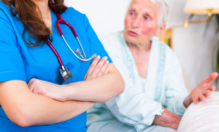 geriatrician: Condident doctor standing next to elderly womans bed who is talking to her.