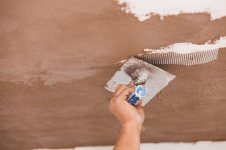 Construction worker skim coating the ceiling after the application of fiberglass net.