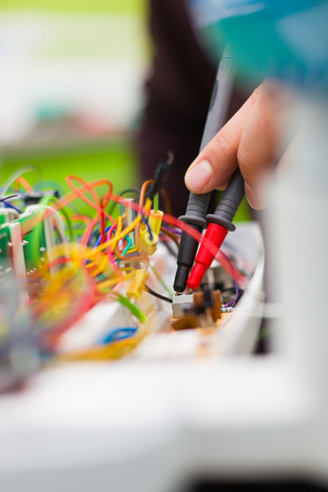 Electrician measuring electrical panels, detecting failure before fixing it.