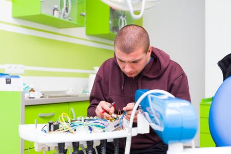 Medische apparatuur engeneer bevestiging van een tandheelkundige stoel in het kantoor van de tandarts.