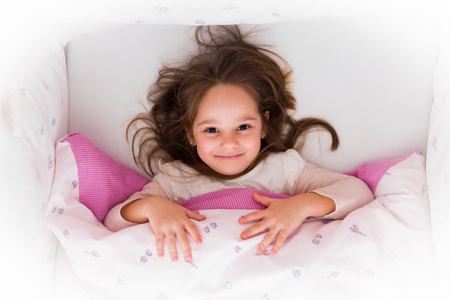 Little girl smiling in bed before getting up. She had a good night.