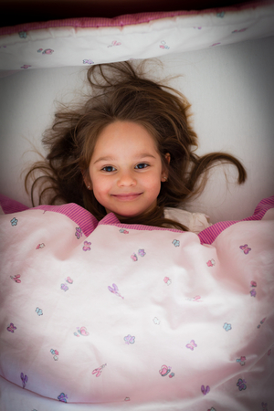 Little girl smiling in bed at night, before sleeping.