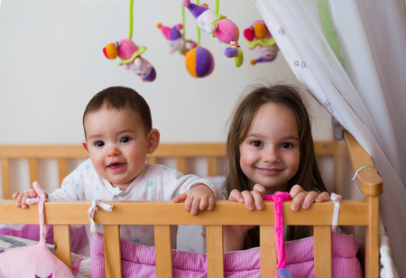 Two beautiful and happy siblings - sisters - waking up / laying down at morning / night. Archivio Fotografico