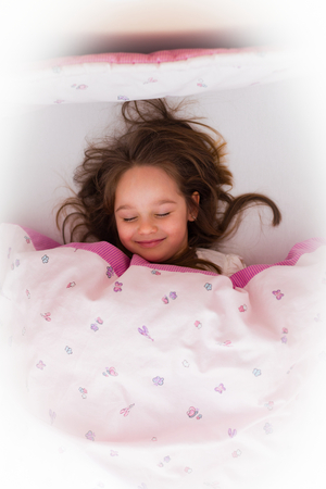 Little girl sleeping late in the morning, dreaming happy dreams.