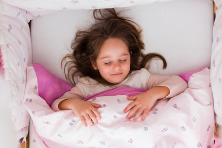 Little brunette girl sleeping in her warm bed.