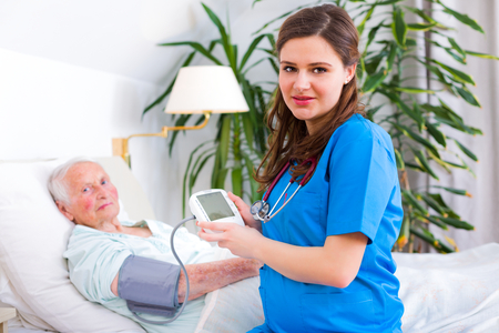 Kind carer measuring the blood pressure of a happy elderly woman in bed in the nursing home.