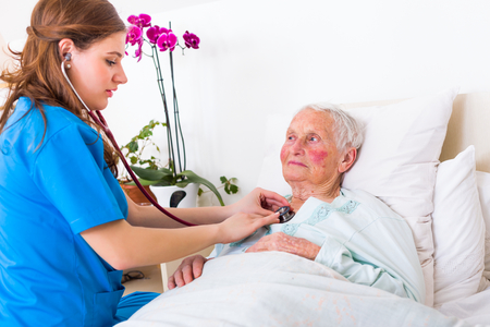 Happy elderly woman assisted by geriartric doctor, examination in the nursing home. Stock Photo