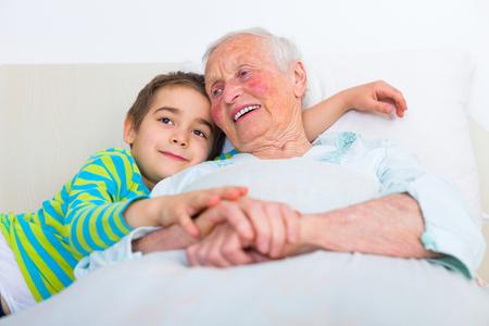 Elderly woman telling bedtime stories for her grandchild before sleeping.