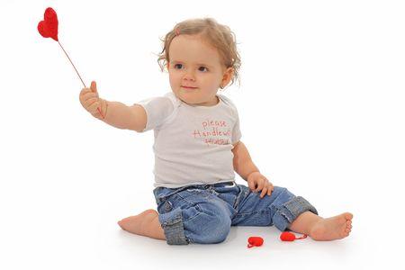 old year: Lovely un anno di et� bambina gioca con il cuore rosso