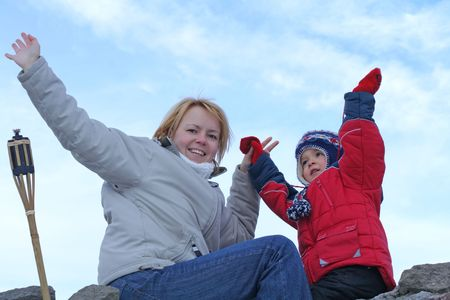 Young women and child on the edge of a stone wall waving Stock Photo - 801178