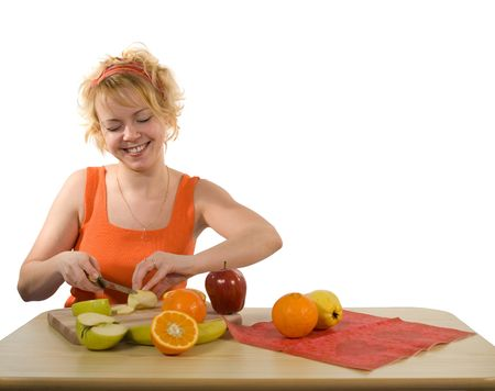 Young blond, happy and healthy looking woman preparing fruit salad (isolated, with copy space) Stock Photo - 789782