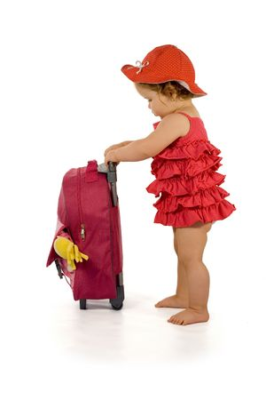 Little girl in purple dress and hat, holding a purple luggage (isolated, with a bit of shadow, clipping path)
