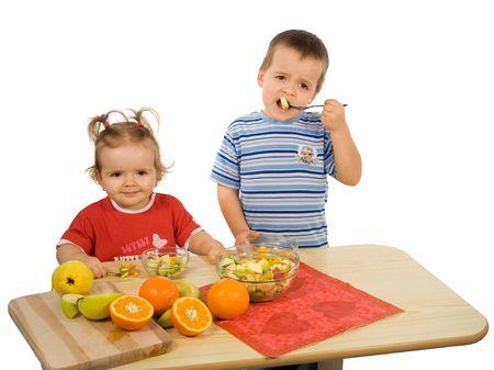 Niños, muchacha y muchacho, comiendo la ensalada de fruta (aislada) Foto de archivo - 829419