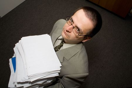 Man working late with papers in the office - looking up (low light portrait) - concept for deadline, stress and hard working Stock Photo - 849996