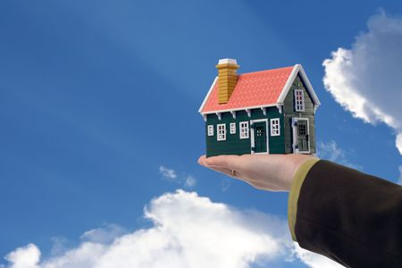 Miniature house in woman hand held against blue skies - real estate concept photo