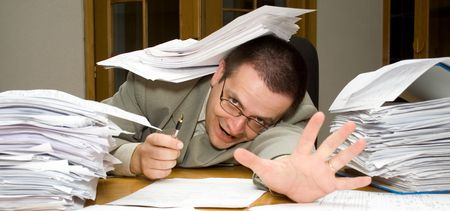 outwork: Desperate businessman reaching for help with paperwork - concept for overtime, deadlines and stress