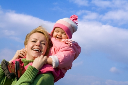 Woman and baby girl having fun outdoors in spring time photo