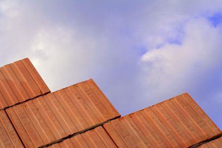 Unfinished brick wall - under construction, against blue sky photo