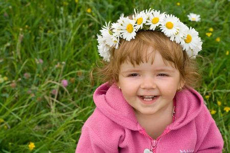 girl with daisy wreath looking up and laughing on the spring meadow full of flowers