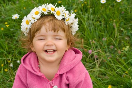 Happy laughing girl with daisy wreath on the spring meadow photo