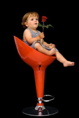 La pequeña muchacha que se sentaba en la silla de eslabón giratorio roja, ofrecimiento se levantó alguien - concepto para el día de las madres - aislada en negro Foto de archivo - 1078577
