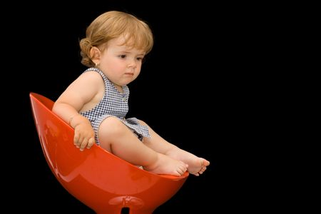 Little girl in a red plastic swivel chair - thinking - isolated on black - copy space Stock Photo - 1118001