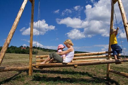 Woman and two children playing on a wooden swing outdoors under a bright blue summer sky photo