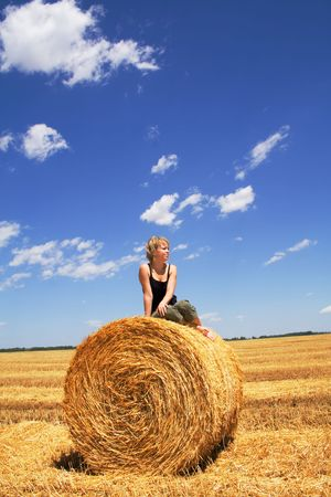 Woman sitting on a hay bale in summer stubble field under a bright vivid sky Stock Photo - 1280587