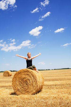 Woman enjoying the summer sun sitting on a hay bale under a bright blue sky Stock Photo - 1280588
