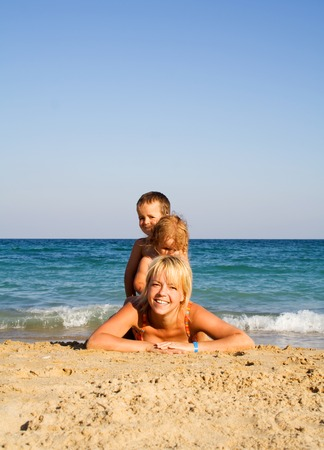Happy mother and kids playing on the sandy beach Stock Photo - 1412961