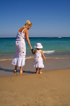 alike: Woman and her little girl walking by the sea in the summer, holding hands, dressed alike