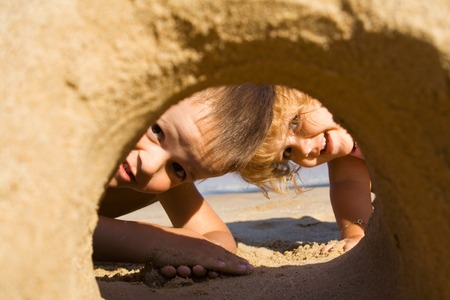 exploring: Two children having fun looking through a sand castle on the beach