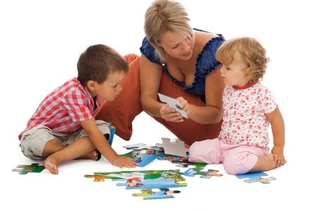 absorbed: Happy mother and children playing with puzzle on the floor - isolated on white, with a bit of shadow