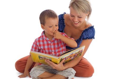poco: Mujer y su pequeño muchacho que tienen diversión el leer de un cuento de hadas - aislado en blanco con un poco sombra Foto de archivo