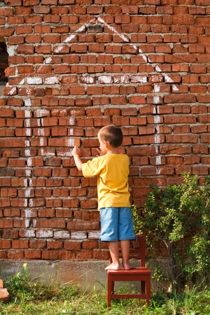 Boy drawing a house on red brick wall - home and real estate concept