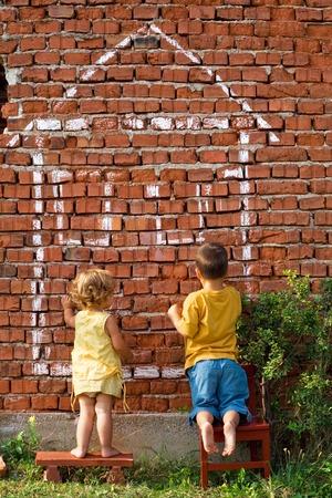 dessin enfants: Deux enfants dessinant la maison dimagination sur un mur de brique - concept de immobiliers Banque d'images