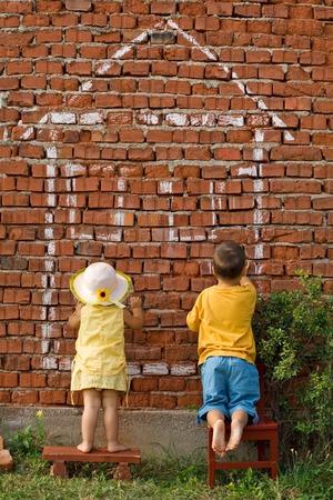 droomhuis: Twee schattige kinderen tekenen hun droom huis - onroerend goed en bancaire concept Stockfoto