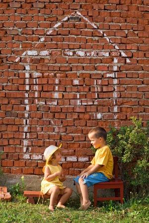 Dos niños hablando de su nuevo hogar - concepto de bienes raíces  Foto de archivo - 1543546