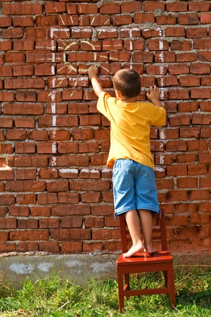 Boy drawing a happy sun in a window on a red brick wall